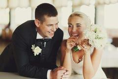 Position de rire de jeunes mariés penchée sur le piano Photos stock