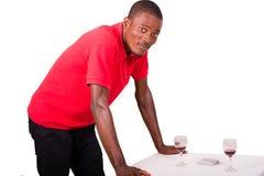 Position de sourire d'homme d'affaires seule contre une table photographie stock