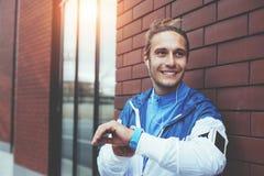 Position de sourire gaie d'athlète sur la rue avec des smartwatches et le brassard heureux avec ses résultats de séance d'entraîn photo libre de droits