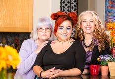Position de sourire de trois femmes dans la cuisine Photo stock