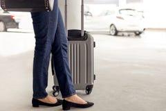 Position de touristes de femme avec le taxi de attente de bagage Images stock