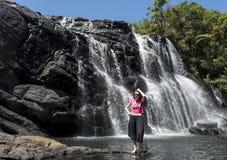Position de touristes de fille près de la belle cascade étonnante énorme photo libre de droits