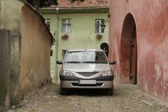 Position de voiture sur la rue dans Sighisoara, Roumanie Détails d'architecture roumaine, de murs et de portes Rue en pierre clas image stock