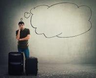 Position de voyageur de jeune homme derrière son bagage et attente image stock