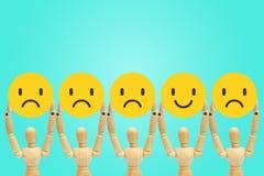 Position en bois de mannequin de figure et tenir des émotions de visage dans la tristesse et le bonheur photographie stock libre de droits