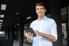 Position et à l'aide de sourire d'homme d'affaires du comprimé près du centre d'affaires Image libre de droits