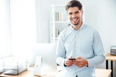Position et à l'aide de sourire d'homme d'affaires du téléphone portable dans le bureau Photographie stock libre de droits