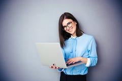 Position et à l'aide de sourire de femme d'affaires de l'ordinateur portable Photos stock