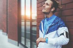 Position fatiguée d'athlète sur la rue avec des smartwatches et le renversement de brassard avec ses résultats de séance d'entraî photographie stock libre de droits