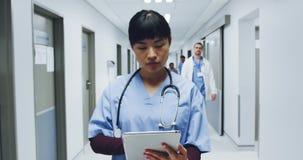 Position femelle de docteur dans le couloir d'hôpital utilisant la tablette 4k banque de vidéos