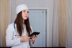 Position femelle de médecin ou d'infirmière avec le stéthoscope et utiliser un comprimé images stock