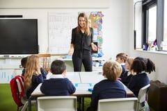 Position femelle de maître d'école dans une salle de classe faisant des gestes aux écoliers, s'asseyant à une écoute de table photo stock