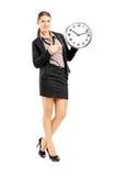 Position femelle de sourire et pointage sur une horloge murale Image stock