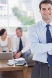 Position gaie d'homme d'affaires tandis que ses collègues travaillent image stock