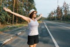 Position heureuse mûre de femme sur la route, bras ouverts de sourire au soleil photos stock