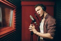 Position impressionnante belle de chanteur avec le microphone dans la salle de enregistrement photographie stock libre de droits