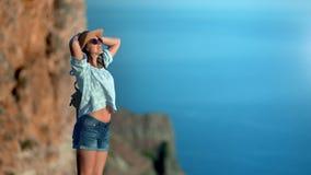 Position la prenant un bain de soleil appréciante femelle de hippie décontracté de voyage sur la montagne admirant la mer banque de vidéos