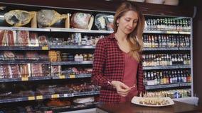 Position mûre de femme au foyer dans l'hypermarché et dégustation du casse-croûte frais banque de vidéos