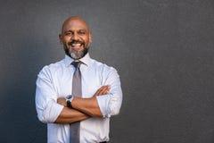 Position mûre heureuse d'homme d'affaires avec les bras pliés photos libres de droits