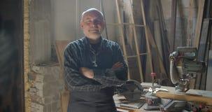 Position masculine d'une chevelure grise supérieure de charpentier à la fabrication en bois avec les bras croisés souriant franch banque de vidéos