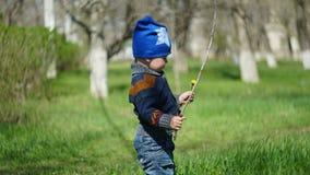 Position mignonne d'enfant en parc avec le bâton photographie stock libre de droits