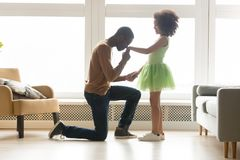 Position noire aimante de père sur la main de participation de genou de la fille photos stock