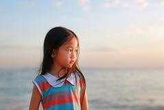 Position paisible de fille de petit enfant sur la plage à la lumière de coucher du soleil avec regarder  image stock