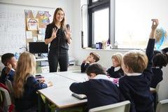Position primaire femelle de maître d'école dans une salle de classe faisant des gestes aux écoliers s'asseyant à une table écout photographie stock libre de droits