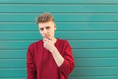 Position réfléchie d'homme sur le fond d'un mur et de regarder de turquoise la caméra avec un regard réfléchi photos stock