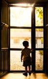 Position rétro-éclairée d'enfant en bas âge devant la porte images libres de droits