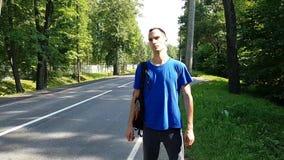 Position sérieuse de voyageur de jeune homme du côté de la route et des crochets une voiture de dépassement Accrocher une conduit banque de vidéos