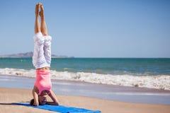 Position sur sa tête à la plage Photos stock