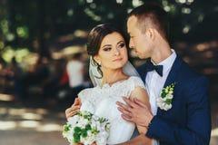 Position tendre d'épaules du ` s de jeune mariée de prises de marié avec elle dans la PA photographie stock libre de droits