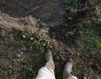 Position vue de mâle adulte avec des bottes près d'une rivière en crue photo stock