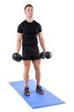 Positionen för shower för den unga mannen krullar den startande av biceps Royaltyfri Bild