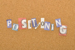 Positioning Word Made From Newspaper Letter. Shot over pinboard background Stock Photography