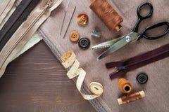 positionnement Ciseaux, boutons, fermeture éclair, ruban métrique, fil et dé dessus Image stock