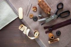 positionnement Ciseaux, boutons, fermeture éclair, ruban métrique, fil et dé dessus Photos stock