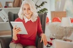 Positiv äldre dam som sitter i stol med minnestavlan royaltyfria bilder