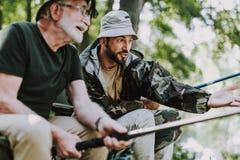 Positiv äldre man och hans son som tillsammans fiskar arkivbild
