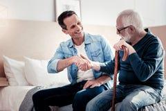 Positiv äldre man som hälsar hans son royaltyfria foton