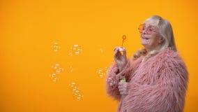 Positiv åldrig kvinna i roligt rosa lag och rund solglasögon som gör såpbubblor stock video