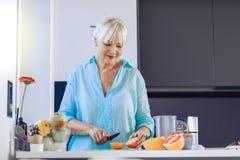 Positiv åldrig kvinna som ser apelsinen arkivbild