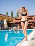 Positiv, überzeugtes blondes Mädchen in einem Bikini auf einem Erholungsorthintergrund Sommermodekonzept Kopieren Sie Platz Lizenzfreie Stockfotos