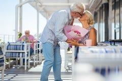 Positiv alterte den Mann, der seiner Frau einen Kuss gibt stockbild
