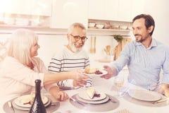 Positiv alterte Eltern enjoyign Mahlzeit mit ihrem erwachsenen Sohn lizenzfreie stockfotografie