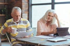 Positiv alterte Paare sititng am Tisch zu Hause Lizenzfreies Stockfoto