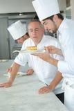 Positiv bagare som kontrollerar den fulländande kakan arkivbilder