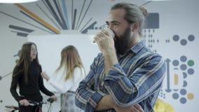 Positiv beardie i den rutiga skjortan som tillbaka dricker kaffeblickar på hans kvinnliga kollegor som pratar i bakgrunden _ stock video