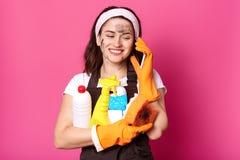 Positiv Caucasian kvinna som talar på mobiltelefonen, medan clening hennes hus och att rymma svampen och tvättmedel i händer som  arkivfoto